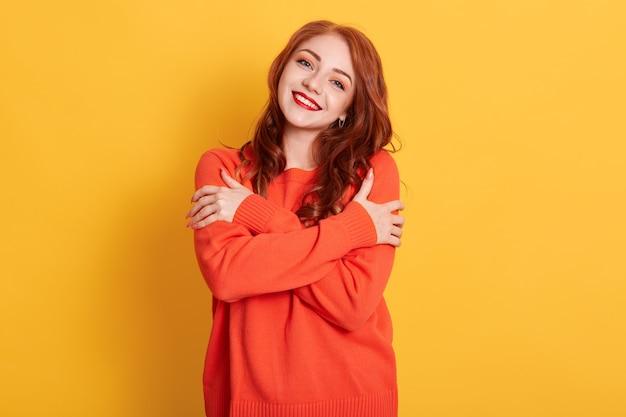 Jovem alegre e romântica expressa amor próprio e carinho, sorri suavemente, usa um macacão laranja enorme e abraça o próprio corpo