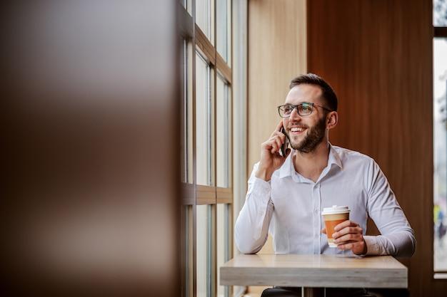 Jovem alegre e sorridente elegantemente vestido, sentado no refeitório ao lado da janela, olhando através dela, segurando uma xícara descartável de café e conversando ao telefone com um amigo.