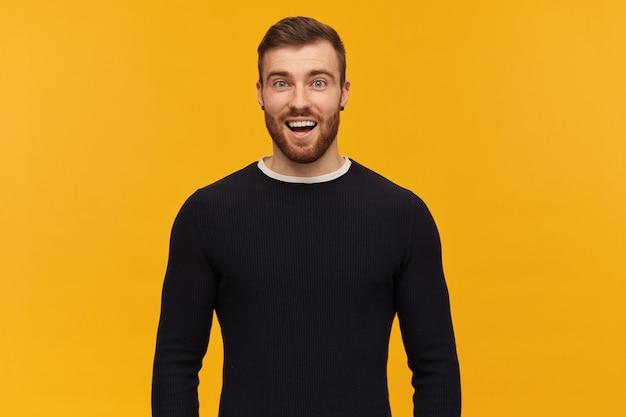 Jovem alegre e surpreso com barba e boca aberta em uma manga comprida preta fica animado e parece surpreso com a parede amarela