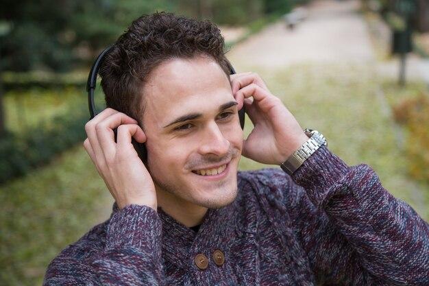Jovem alegre em pé e ouvindo música com fones de ouvido no parque outono.