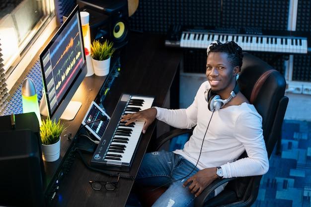 Jovem alegre em roupas casuais, olhando para a câmera enquanto trabalhava em uma nova música em frente ao monitor do computador no estúdio