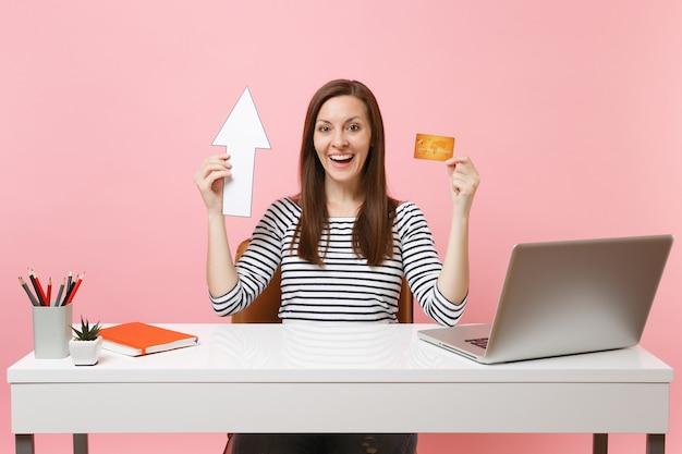 Jovem alegre em roupas casuais segurando seta, cartão de crédito, sentada no trabalho na mesa branca com laptop pc contemporâneo
