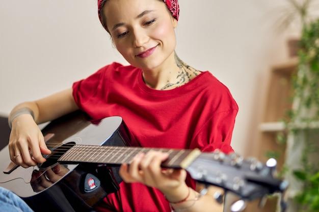 Jovem alegre em roupas casuais, sorrindo enquanto tocava violão em casa