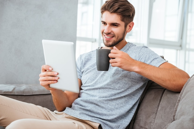 Jovem alegre em t-shirt cinza, sentado no sofá em casa. comunicação por tablet e sorrindo enquanto bebe um café.