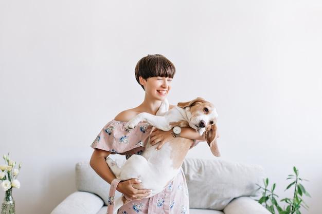 Jovem alegre em um relógio de pulso da moda segurando seu cachorrinho com nariz preto e rindo