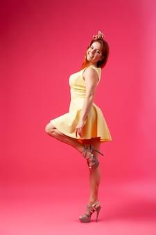 Jovem alegre em um vestido amarelo brilhante no estilo de um novo arco posando e sorrindo em rosa