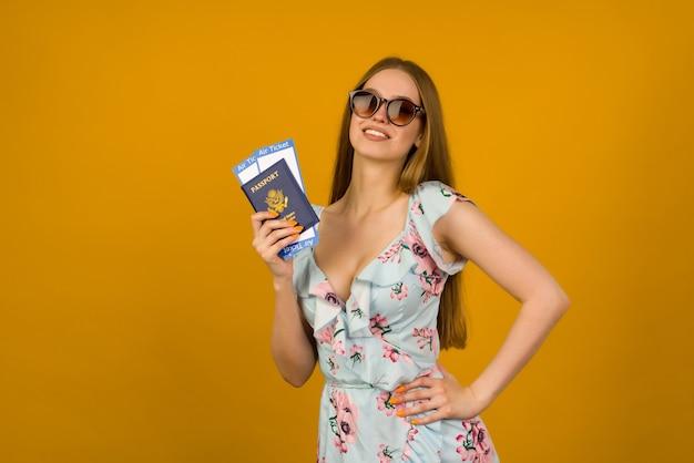 Jovem alegre em um vestido azul com flores e óculos de sol está segurando as passagens aéreas com um passaporte com um fundo amarelo. alegra-se com a retomada do turismo após a pandemia do coronovírus.
