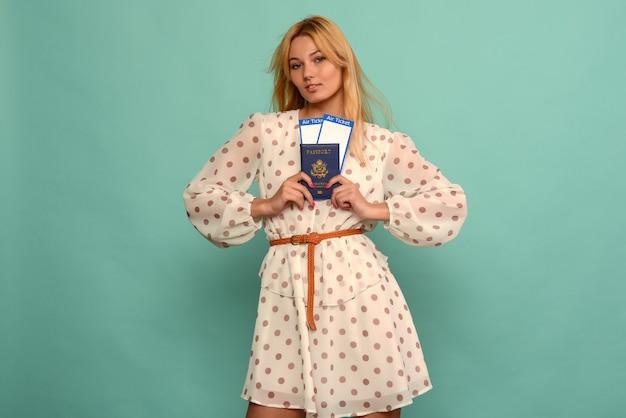 Jovem alegre em um vestido de bolinhas está segurando as passagens aéreas com um passaporte com um fundo azul.