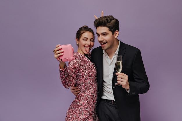 Jovem alegre em um vestido rosa glitter fazendo selfie com o namorado, vestindo camisa branca, terno preto e segurando uma taça de champanhe