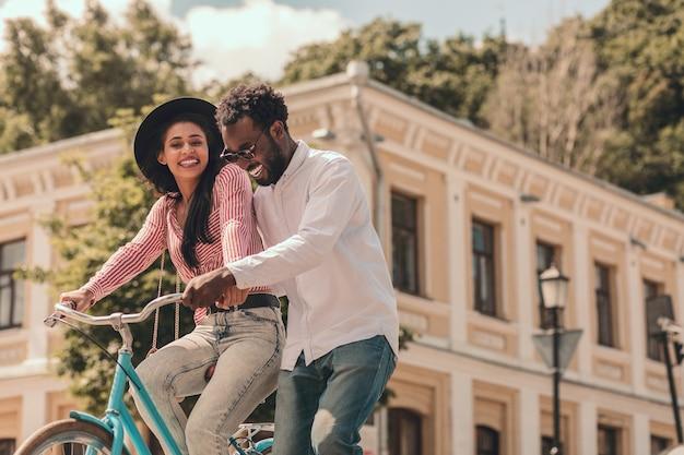 Jovem alegre em uma bicicleta e seu namorado feliz ao lado dela