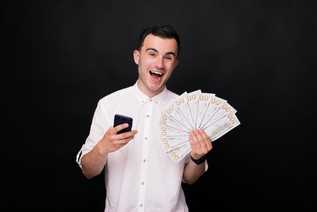 Jovem alegre em uma camisa branca mantém um telefone e algumas contas em fundo preto