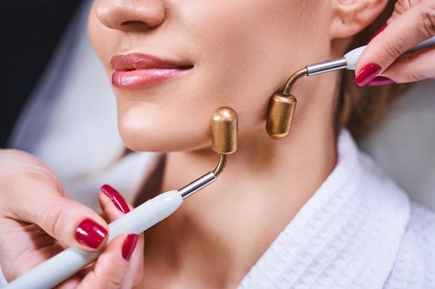 Jovem alegre em visita a um salão de beleza para tratar seu rosto com microcorrentes com ajuda de especialista