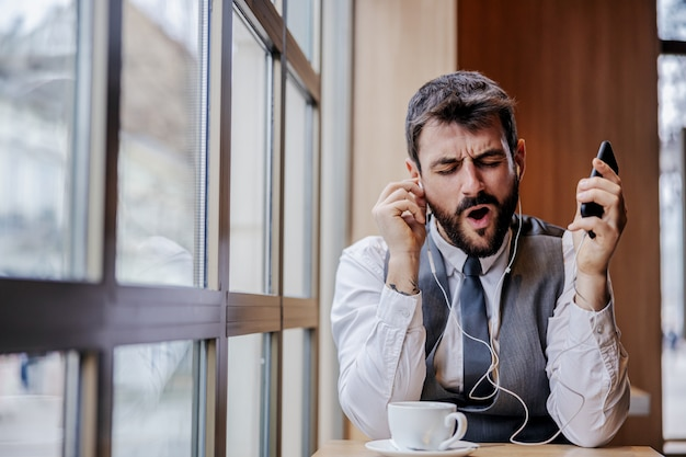 Jovem alegre empresário barbudo sentado no refeitório, ouvindo música por telefone inteligente e cantando.