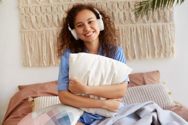 Jovem alegre encaracolada afro-americana sentada na cama, abraçando um travesseiro, ouvindo a música favorita em fones de ouvido, sorrindo amplamente e parece feliz.