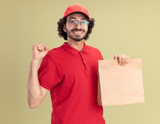 Jovem alegre entregador caucasiano de uniforme vermelho e boné de óculos, segurando um pacote de papel, fazendo gesto de ser forte