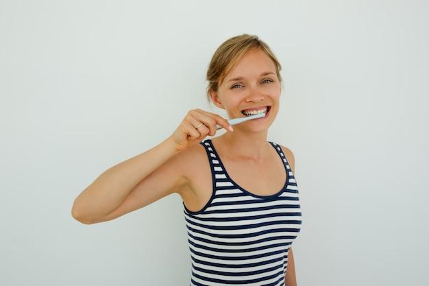 Jovem alegre, escovando os dentes e olhando a câmera. feliz menina saudável esfregando dentes com escova de dentes equipada com dente de dente. conceito de rotina de higiene bucal