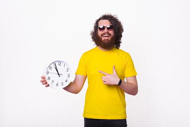 Jovem alegre está apontando para um relógio de parede.