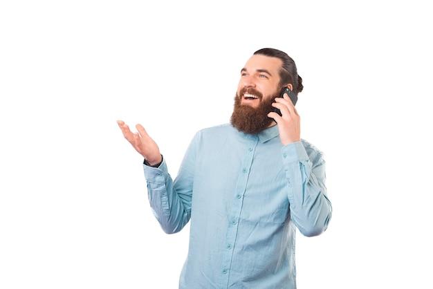 Jovem alegre está falando ao telefone enquanto sorri e gesticula.
