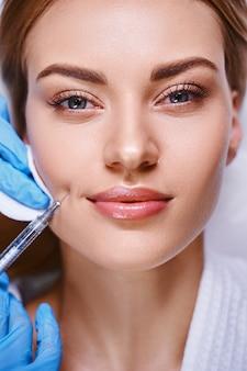 Jovem alegre está fazendo rejunivação na clínica de cosmetologia e usando ácido hialurônico em seringa