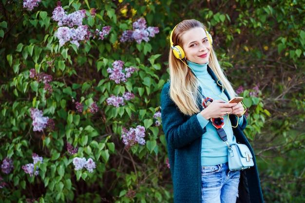 Jovem alegre está ouvindo a música em pé na frente do arbusto lilás