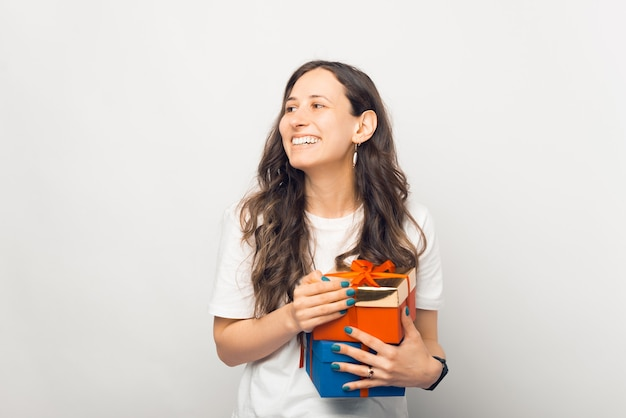 Jovem alegre está segurando duas caixas de presentes, olhando de lado.