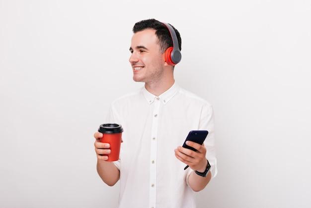 Jovem alegre está segurando um copo de bebida quente e um telefone com fones de ouvido na cabeça, ouvindo a música no fundo branco.