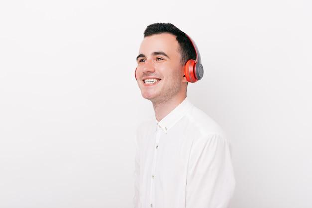 Jovem alegre está sorrindo e ouvindo a música em um fundo branco.