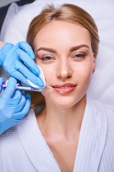 Jovem alegre está vindo ao cosmetologista para procedimentos antiidade e para preenchimento da bochecha