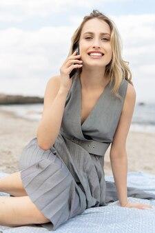 Jovem alegre falando ao telefone inteligente com um grande sorriso na praia