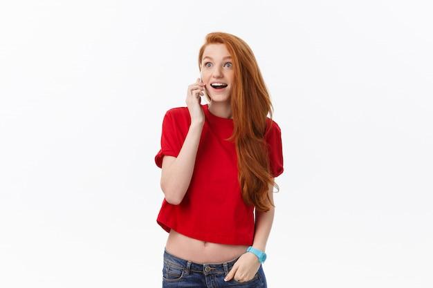 Jovem alegre falando no celular isolado na cinza
