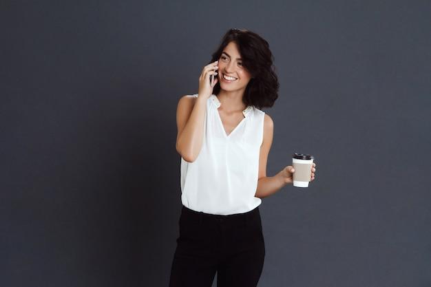 Jovem alegre falando no telefone e segurando o café na mão