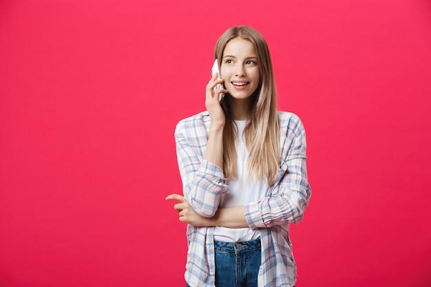 Jovem alegre falando no telefone móvel isolado no fundo rosa