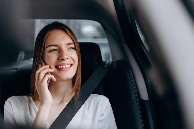 Jovem alegre falando um smartphone sentado no carro.