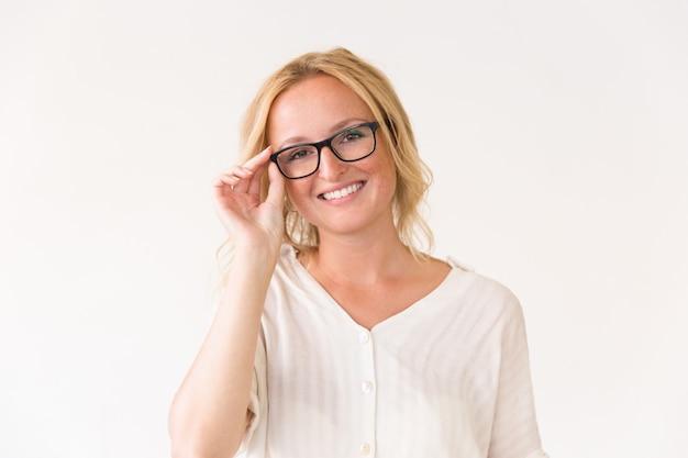 Jovem alegre feliz ajustando os óculos dela