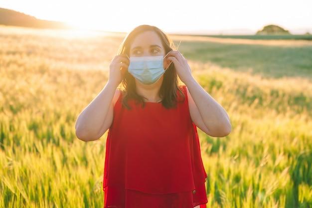 Jovem alegre feliz removendo a máscara facial médica, de pé no prado ao ar livre durante o pôr do sol
