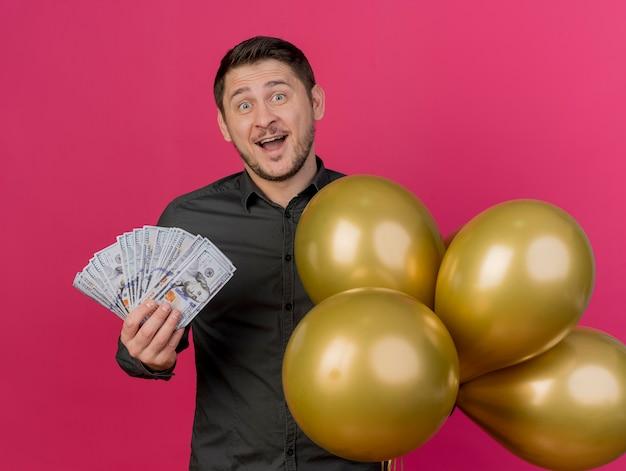 Jovem alegre festeiro, vestindo uma camisa preta segurando dinheiro com balões isolados em rosa