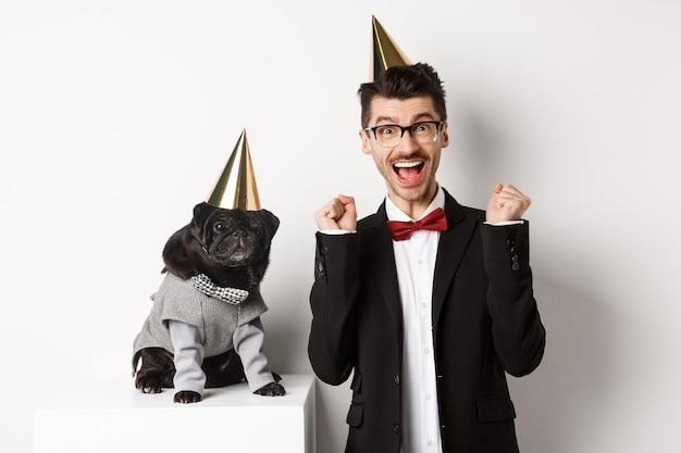 Jovem alegre gritando de alegria, cachorro e dono usando cones de festa de aniversário e comemorando, cara se alegrando e olhando para a câmera, fundo branco