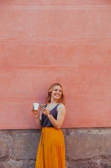 Jovem alegre isolada em uma parede usando seu telefone