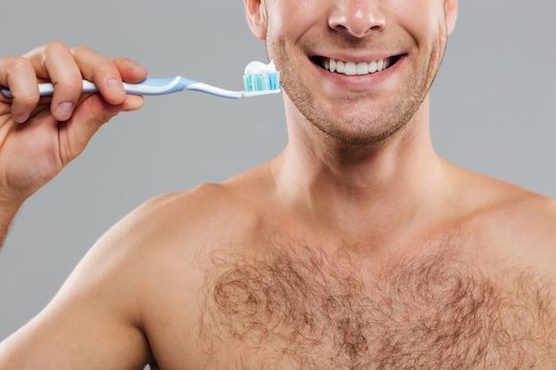 Jovem alegre limpando os dentes com escova e pasta de dentes e sorrindo
