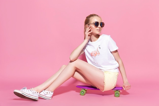 Jovem alegre loira com um skate no fundo rosa.