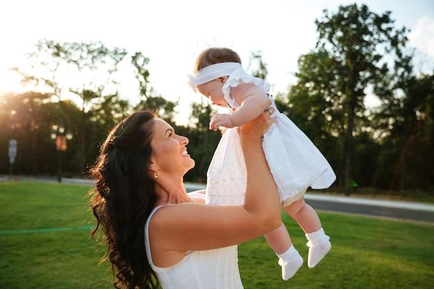 Jovem alegre mãe brincando com sua filha no parque