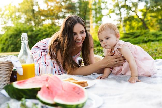 Jovem alegre mãe com sua filha no parque