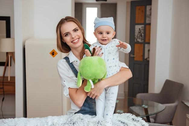 Jovem alegre mãe de pé e segurando seu filho pequeno com um brinquedo em casa