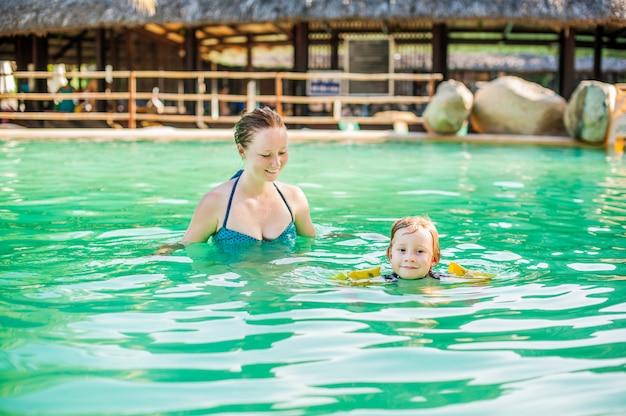 Jovem alegre mãe e filho em uma piscina