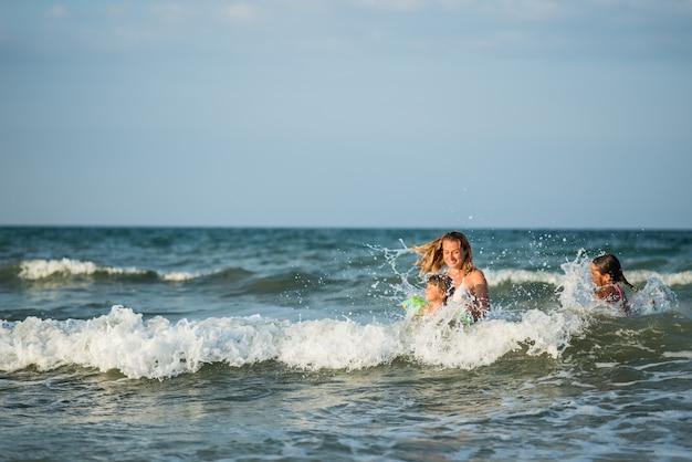 Jovem alegre mãe nadando no mar com suas filhas encantadoras e aproveitando o tão esperado fim de semana em um ensolarado dia de verão