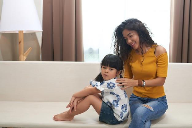 Jovem alegre mãe vietnamita sentada no sofá segurando a filha ressentida enquanto conversa com ela