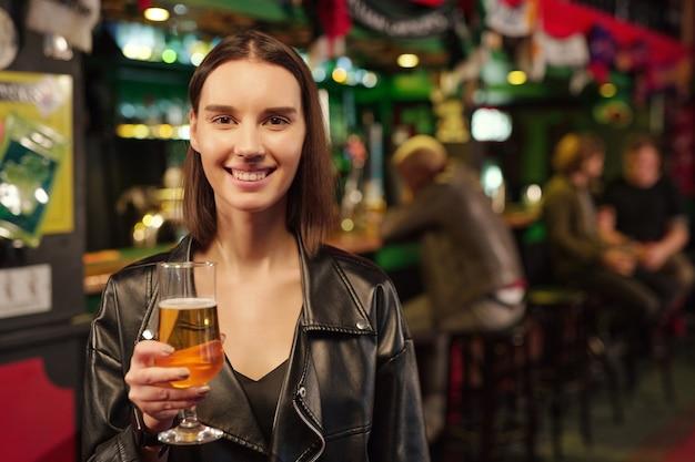 Jovem alegre morena olhando para você enquanto brindava com um copo de cerveja na frente da câmera contra os caras sentados no balcão do bar