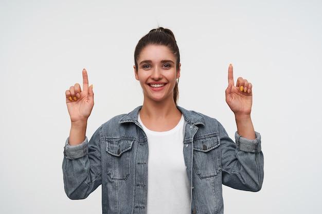 Jovem alegre morena usa camiseta branca e jaquetas jeans, olha para a câmera e sorri amplamente, aponta os dedos para cima no espaço da cópia, fica sobre um fundo branco.