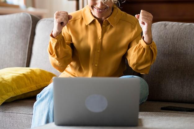 Jovem alegre mostrando o punho com as duas mãos enquanto trabalhava no laptop, sentado no sofá em casa. mulher excitada usando laptop enquanto woking. mulher feliz relaxando no sofá com o laptop na mesa.