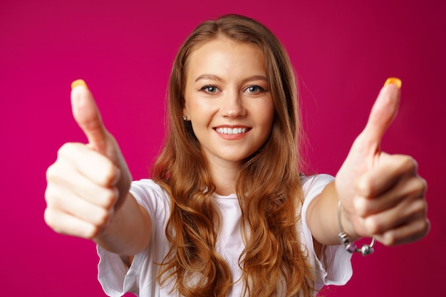 Jovem alegre mostrando sinal de positivo contra rosa